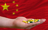 Holding pills in hand in front of china national flag — Stock Photo