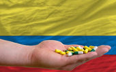 Holding pills in hand in front of colombia national flag — Stock Photo
