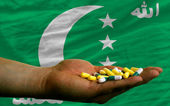 Holding pills in hand in front of comoros national flag — Stock Photo