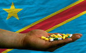 Holding pills in hand in front of congo national flag — Stock Photo
