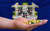 Holding pills in hand in front of connecticut us state flag — Stock Photo