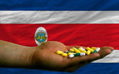 Holding pills in hand in front of costa rica national flag — Stock Photo