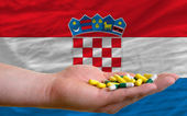 Holding pills in hand in front of croatia national flag — Stock Photo