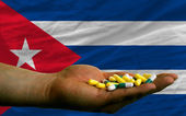 Holding pills in hand in front of cuba national flag — Stock Photo