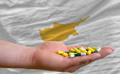 Holding pills in hand in front of cyprus national flag — Stock Photo