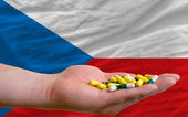 Holding pills in hand in front of czech national flag — Stock Photo
