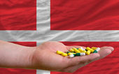 Holding pills in hand in front of denmark national flag — Stock Photo