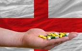 Holding pills in hand in front of england national flag — Stock Photo