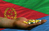 Holding pills in hand in front of eritrea national flag — Stock Photo