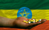 Holding pills in hand in front of ethiopia national flag — Stock Photo