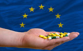 Holding pills in hand in front of europe national flag — Stock Photo
