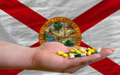 Holding pills in hand in front of florida us state flag — Stock Photo