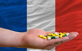 Holding pills in hand in front of france national flag — Stock Photo