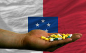 Holding pills in hand in front of franceville national flag — Stock Photo