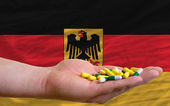 Holding pills in hand in front of germany national flag — Stock Photo