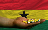 Holding pills in hand in front of ghana national flag — Stock Photo