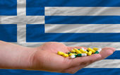 Holding pills in hand in front of greece national flag — Stock Photo