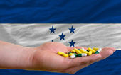 Holding pills in hand in front of honduras national flag — Stock Photo