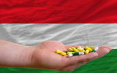 Holding pills in hand in front of hungary national flag — Stock Photo