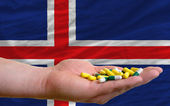 Holding pills in hand in front of iceland national flag — Stok fotoğraf