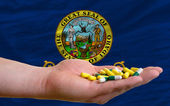 Holding pills in hand in front of idaho us state flag — Stock Photo