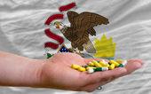 W ręku trzyma tabletki przed illinois nas flaga państwowa — Zdjęcie stockowe