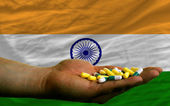 Holding pills in hand in front of india national flag — Stock Photo