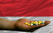 Holding pills in hand in front of indonesia national flag — Stock Photo