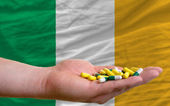 Holding pills in hand in front of ireland national flag — Stock Photo