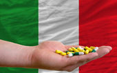 Holding pills in hand in front of italy national flag — Stock Photo