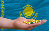 Holding pills in hand in front of kazakhstan national flag — Stock Photo