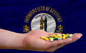 Holding pills in hand in front of kentucky us state flag — Stock Photo