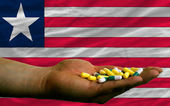 Holding pills in hand in front of liberia national flag — Stock Photo