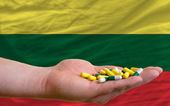 Holding pills in hand in front of lithuania national flag — Stock Photo