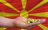 Holding pills in hand in front of macedonia national flag — Stock Photo