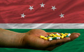 Holding pills in hand in front of maghreb national flag — Stock Photo