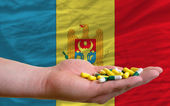 Holding pills in hand in front of moldova national flag — Stock Photo
