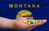Holding pills in hand in front of montana us state flag — Stock Photo