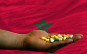 Holding pills in hand in front of morocco national flag — Stock Photo