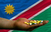 Holding pills in hand in front of namibia national flag — Stock Photo