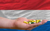 Holding pills in hand in front of netherlands national flag — Stock Photo