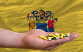 Holding pills in hand in front of new jersey us state flag — Stock Photo