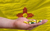 Holding pills in hand in front of new mexico us state flag — Stock Photo