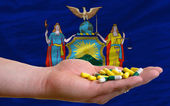 Holding pills in hand in front of new york us state flag — Stock Photo