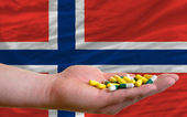 Holding pills in hand in front of norway national flag — Stock Photo