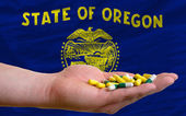 Holding pills in hand in front of oregon us state flag — Stock Photo