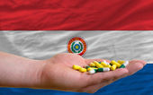 Holding pills in hand in front of paraguay national flag — Stock Photo
