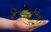 Holding pills in hand in front of pennsylvania us state flag — Stock Photo