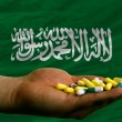 Stock Photo: Holding pills in hand in front of saudi arabinational flag