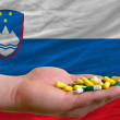 Stock Photo: Holding pills in hand in front of sloveninational flag